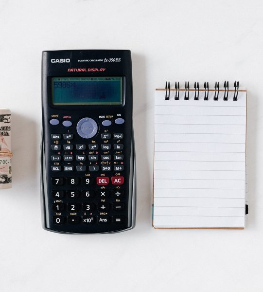 composition-of-calculator-with-paper-money-and-notebook-with-4386341