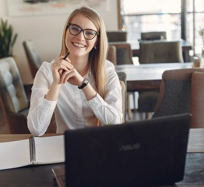 cheerful-young-businesswoman-in-eyeglasses-during-remote-3874619